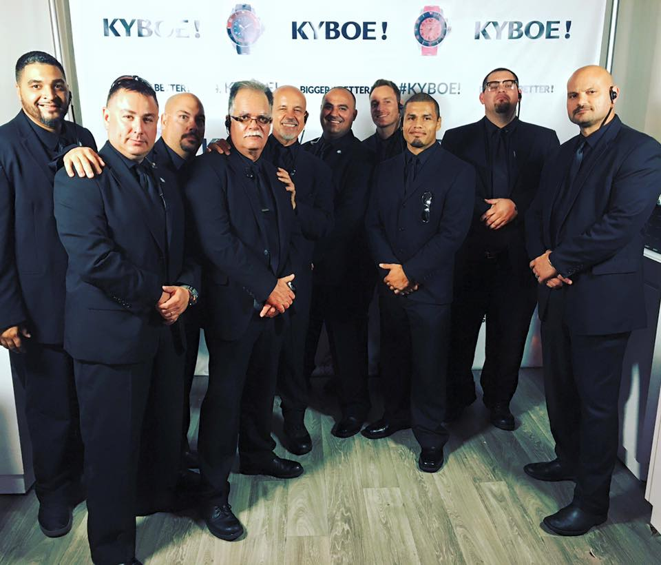 Image is of group of security guards at an event. There is roughly 20 security guards in all black.
