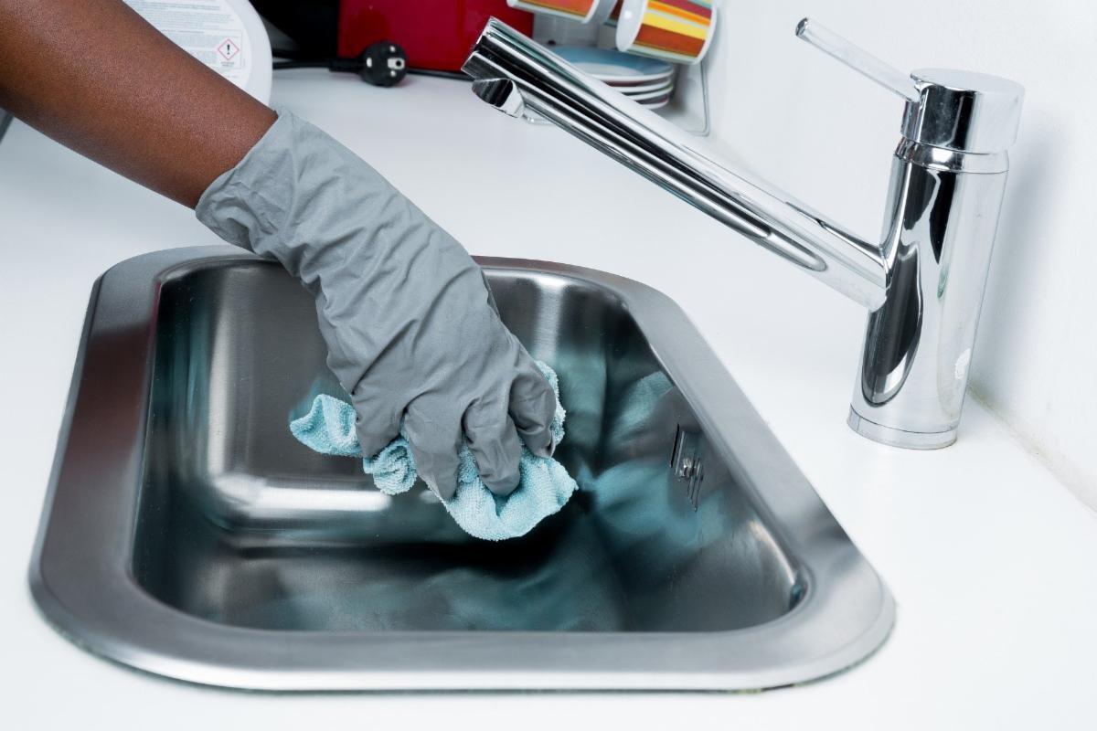 Gloved hand scrubbing a kitchen sink