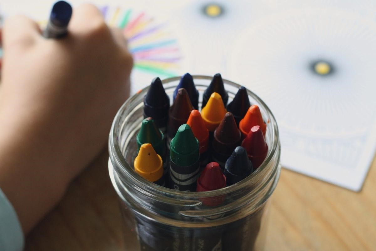 Glass Jar of Crayons with a hand drawing in the background