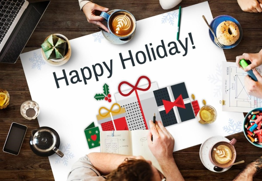 People seated at a table with coffee mugs and a sign reading Happy Holidays on the center of the table