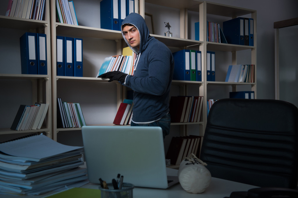 Image is a a man in a hoodie that appears he is stealing books or documents from an office.