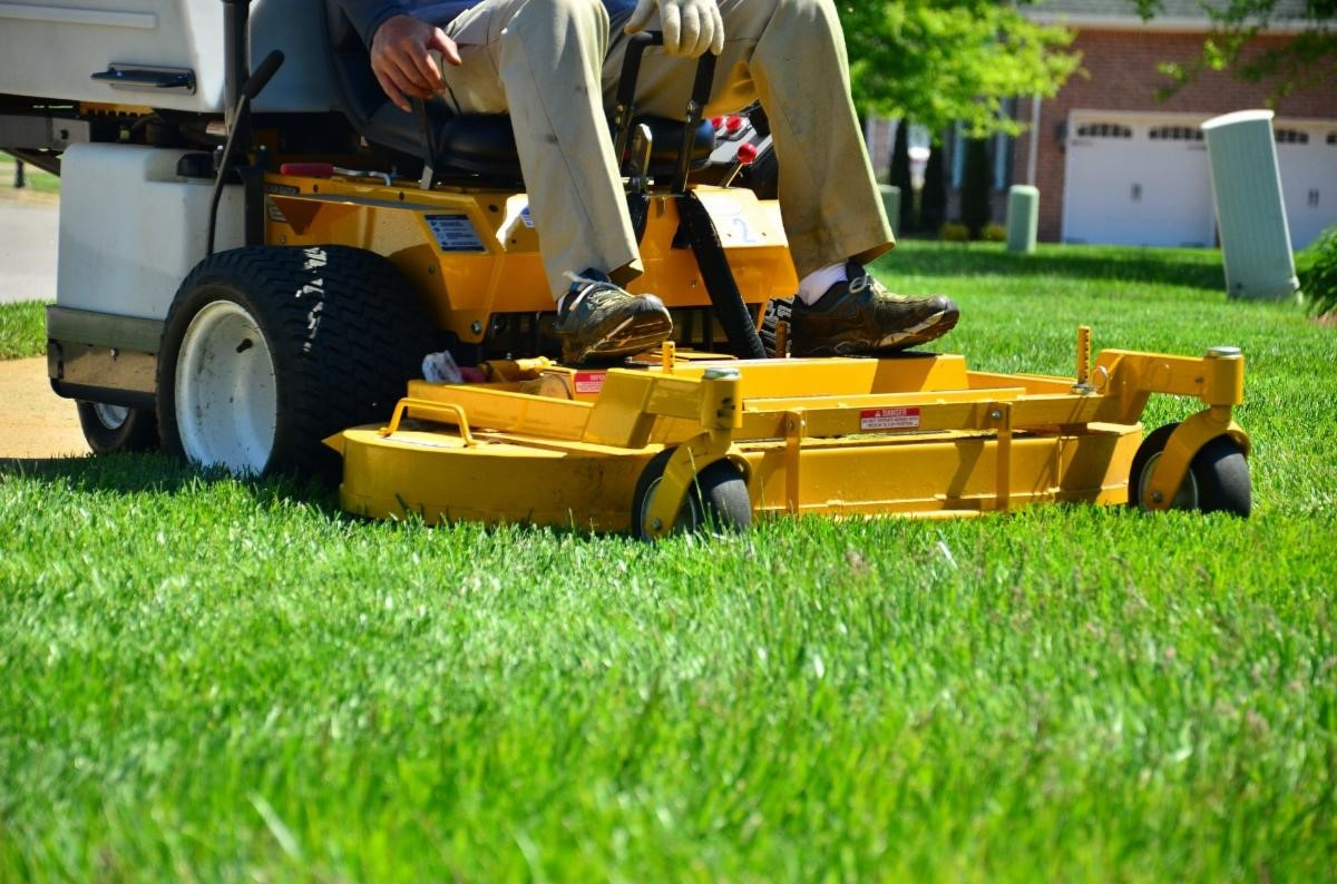 Close up, ground view of a riding lawn mower over grass