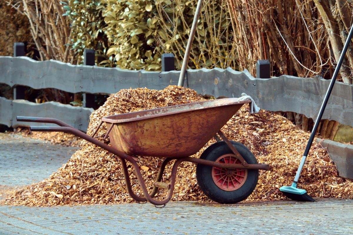 Wheelbarrow in front of a pile of mulch