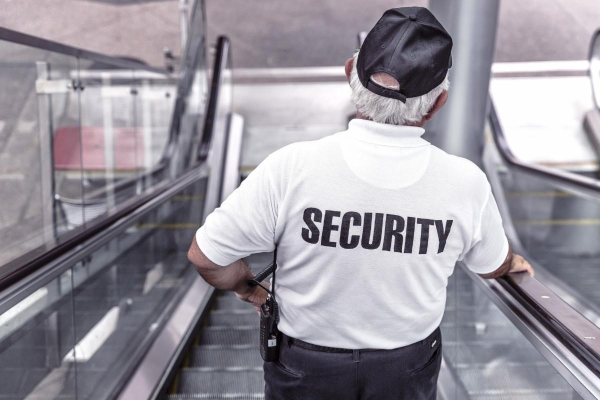 """Man descends escalator wearing a shirt with """"Security"""" printed on the back"""