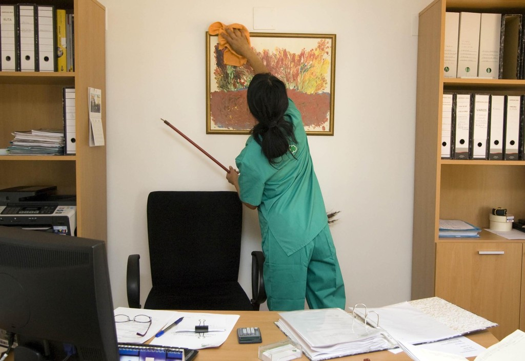 Image is of a woman who has her back turned to us, she is cleaning a picture frame that is hung in an office. The office has 2 bookshelves located on the sides of the painting and you can see a desk cluttered with paperwork, a computer, glasses, calculator and a desk chair behind the desk.