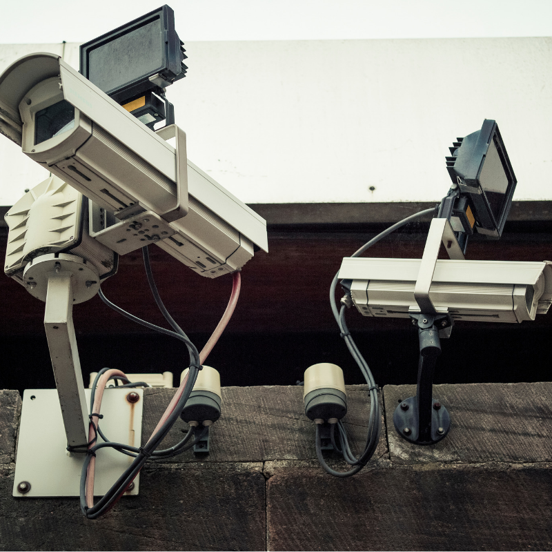 Close up of two security camera outside attached to a building.